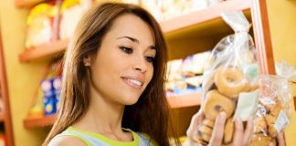 Woman looking at nutrition label on pack of bagels